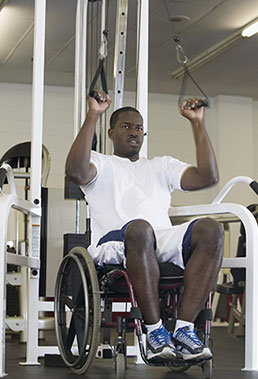 man in wheelchair using fitness equipment in gym